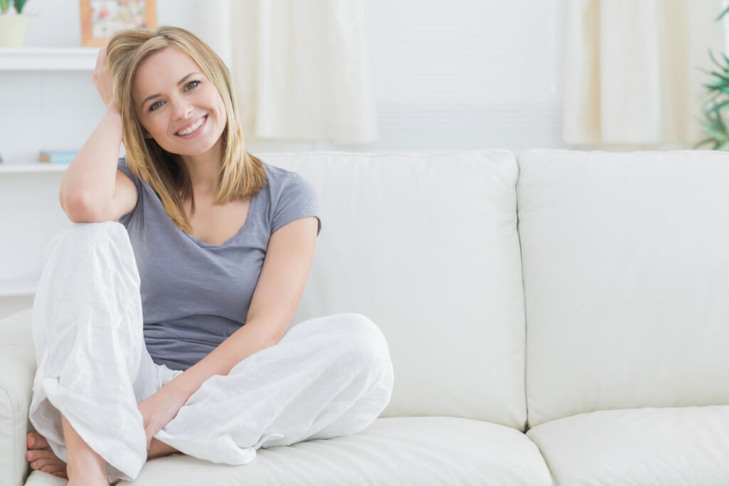 זכות האישה להתגורר באותו בית | אישה שמחה על הספה בבית