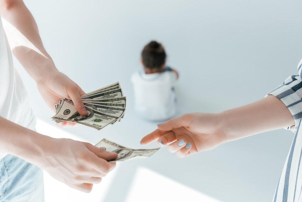 קביעת מזונות ילדים | גבר מביא כסף לאישה עם ילד ברקע